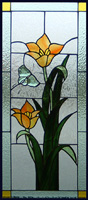 Butterfly bevel with orange tulips made up this stained glass panel, light and dark green with gluechip textured background.